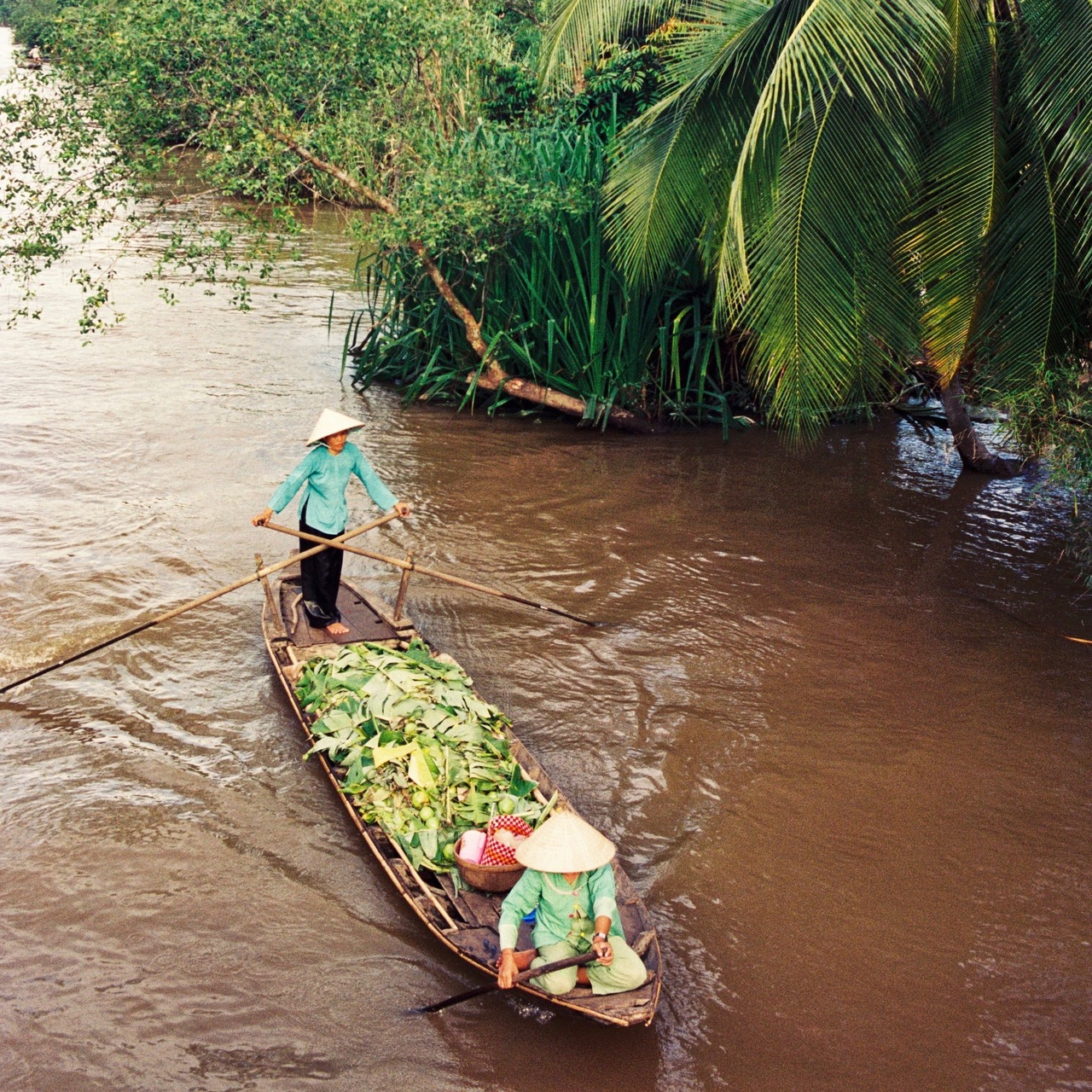 Woman padding a boat with vegetables in Vietnam