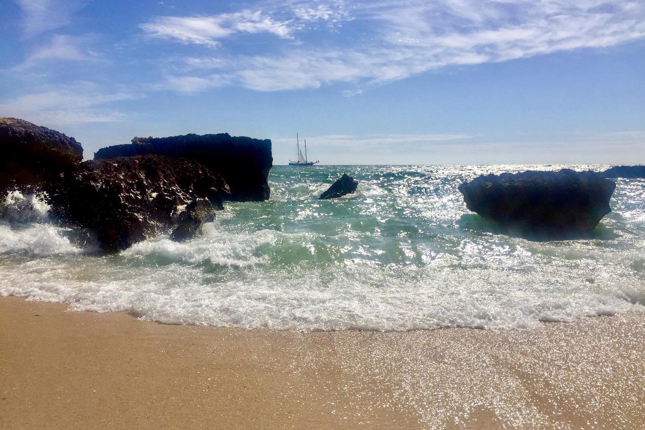 Windy beach and sail boat at Praia do Evaristo, Algarve, Portugal