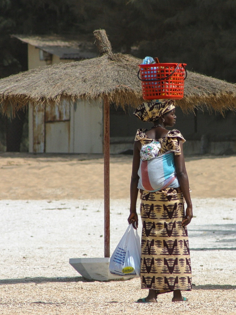 Woman carries baby and stuff in traditional way in Gambia