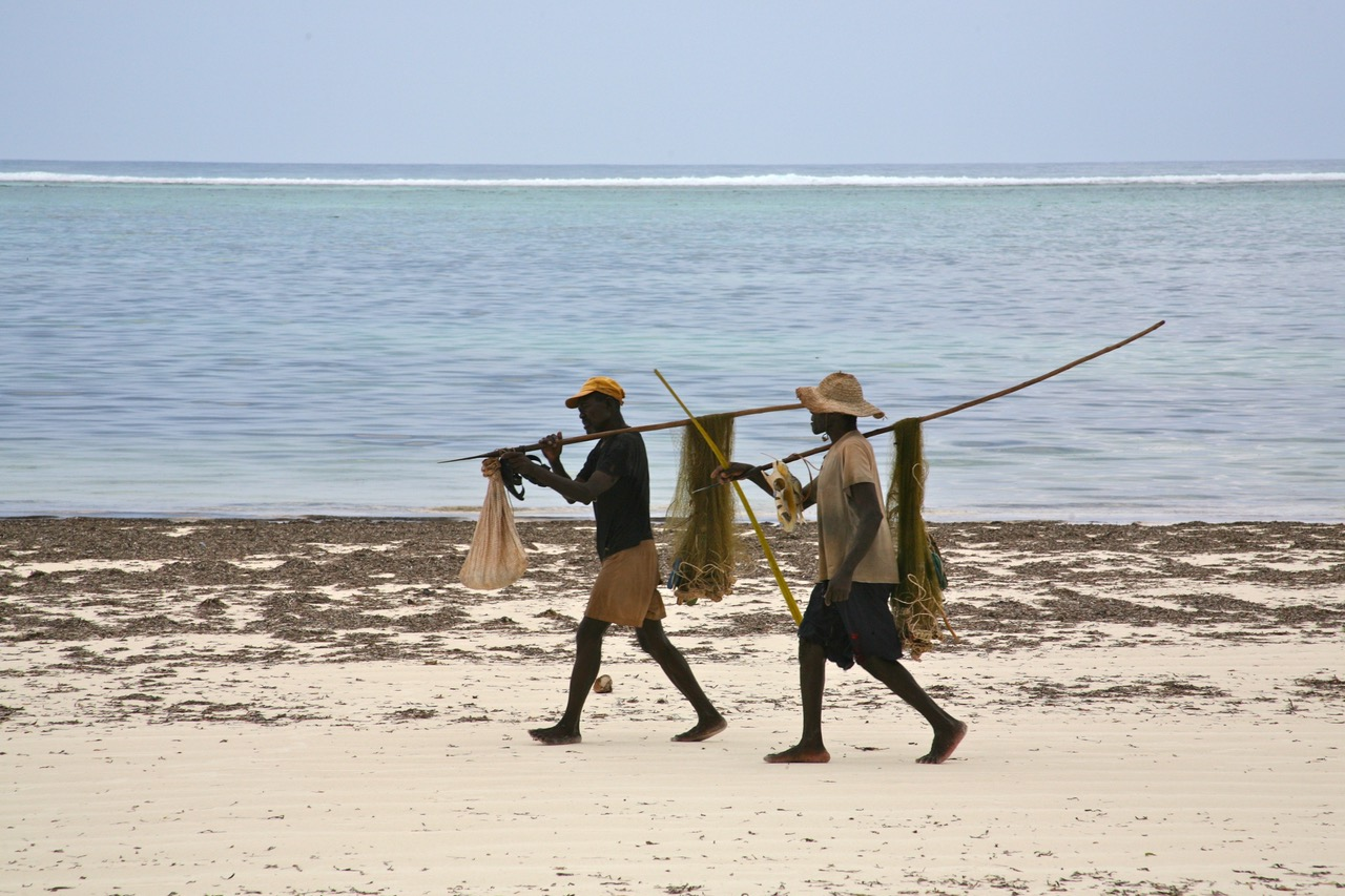 Men on the move on Matemwe Beach, Zanzibar