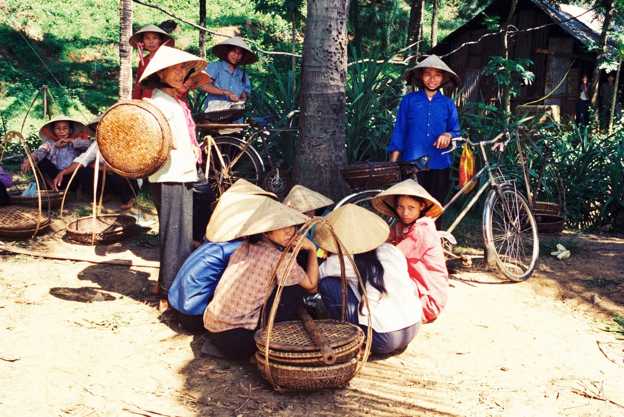 Vietnamese women sitting down at the street market in Hue, Vietnam