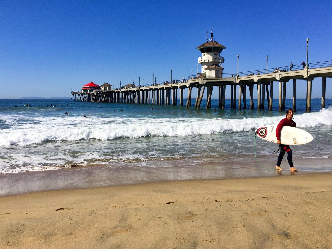 Surfer near pier in Huntington Beach