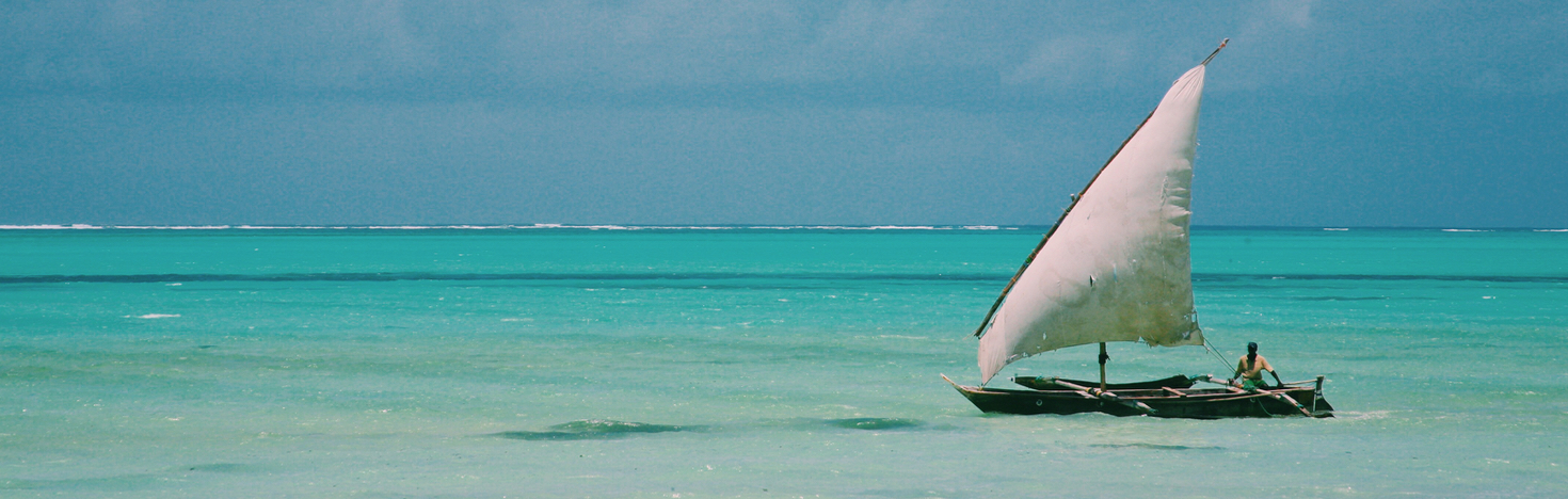 Zanzibar coast line view at Paje Beach with a Dhow boat sailing by